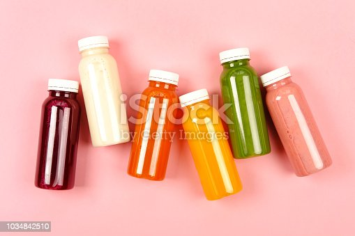 Bottles of multicolored smoothies or juices on pink background. Flat lay style.