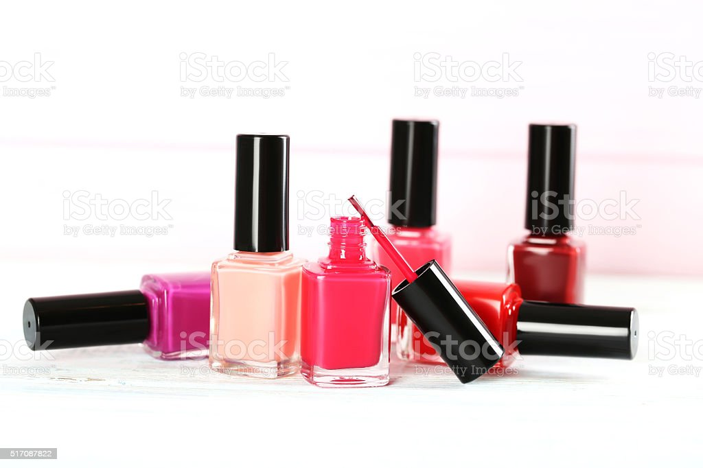 Bottles of nail polish on a wooden table stock photo