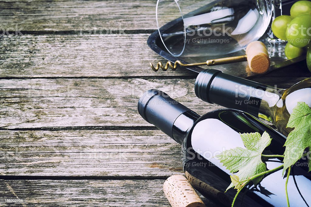 Bottles of red and white wine against wooden background royalty-free stock photo