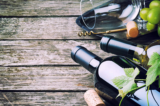 Bottles of red and white wine against wooden background stock photo