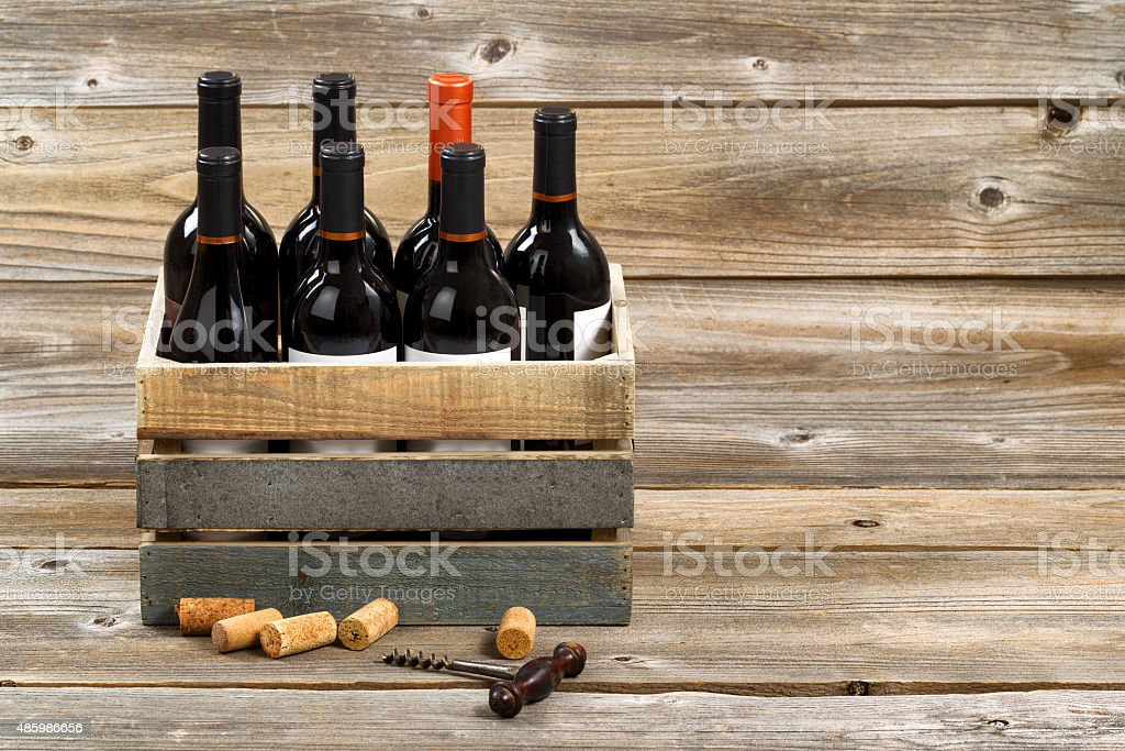 Bottles of red wine in wooden crate on  wooden boards stock photo