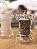 Bottles of salt and pepper on wooden table with blur and bokeh background
