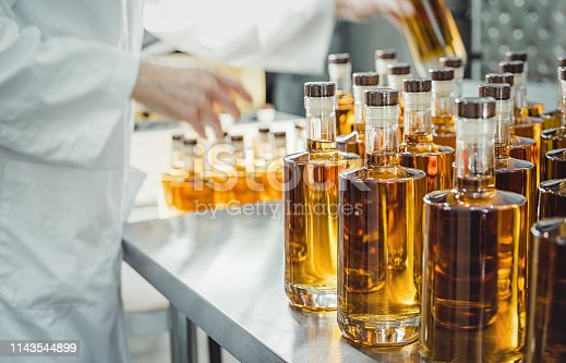 Small liquor production based on maple syrup. Multitude of pure alcohol bottles  not labeled. Bottles placed in a row. one person working in alcohol industry, blurred motion.