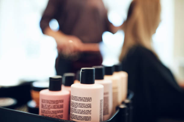 Bottles of styling products in a hair salon Closeup of shampoo and conditioner bottles on a tray in a hair salon with a hairdresser styling a client's hair in the background for sale stock pictures, royalty-free photos & images