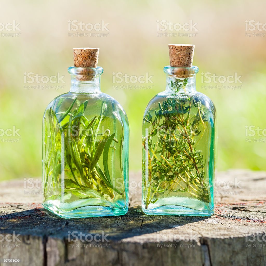 Bottles of thyme and rosemary essential oil or infusion outdoors stock photo