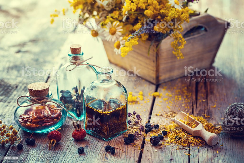 Bottles of tincture and healthy herbs in box stock photo