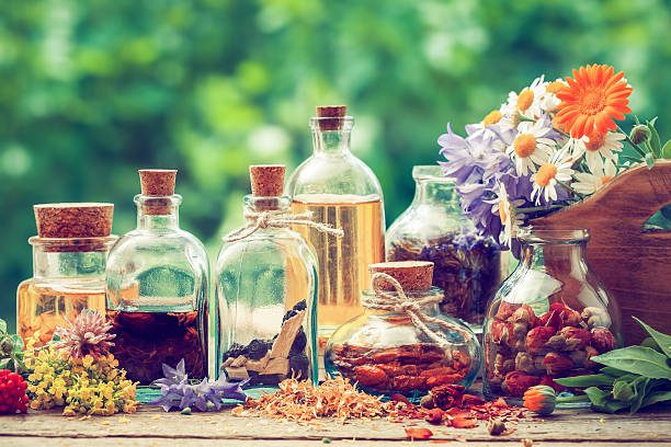 bottles of tincture or potion and dry healthy herbs - aromaterapi stok fotoğraflar ve resimler
