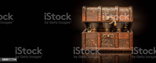 Bottles of tincture or potion in a retro styled.old treasure chest on black wide background - panorama - copy space