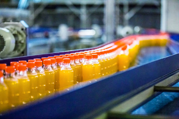 bottles on conveyor belt in factory - bottling plant stock photos and pictures
