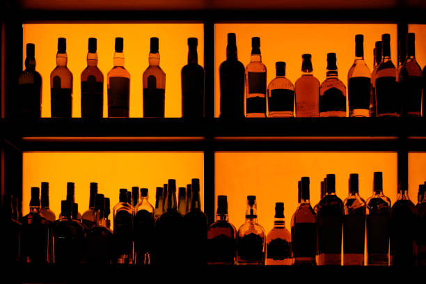 Bottles sitting on shelf in a bar stock photo