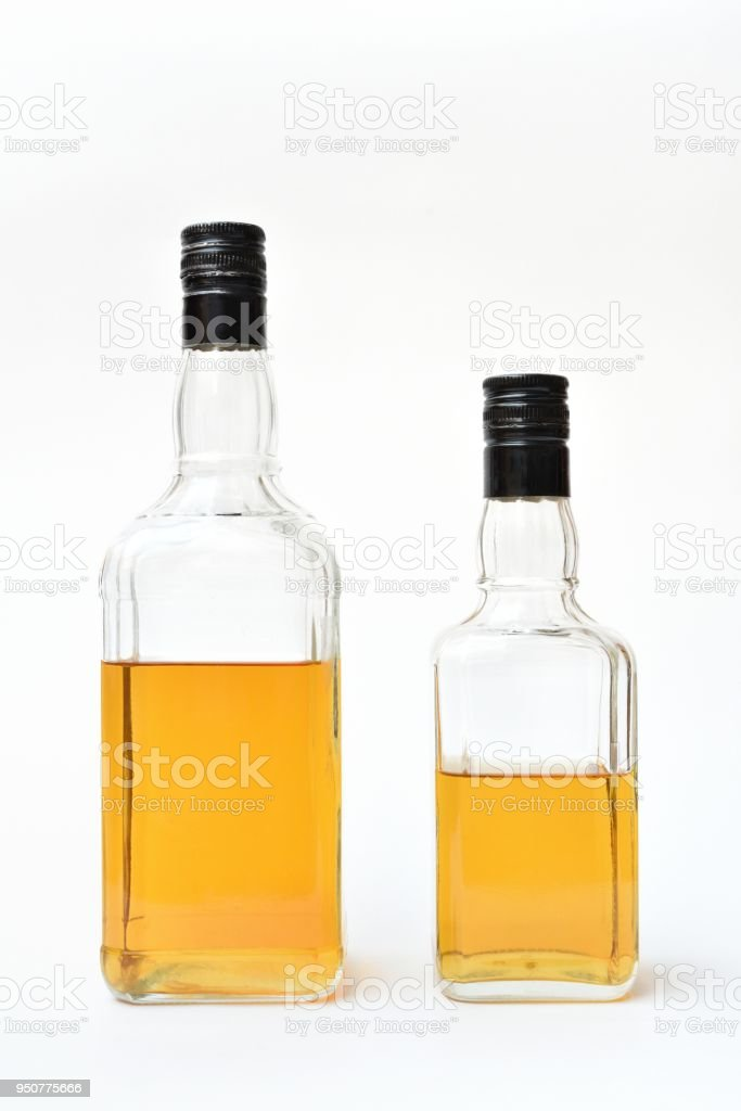Bottles with alcohol, started. Semi-empty bottles with alcohol on a white background. stock photo