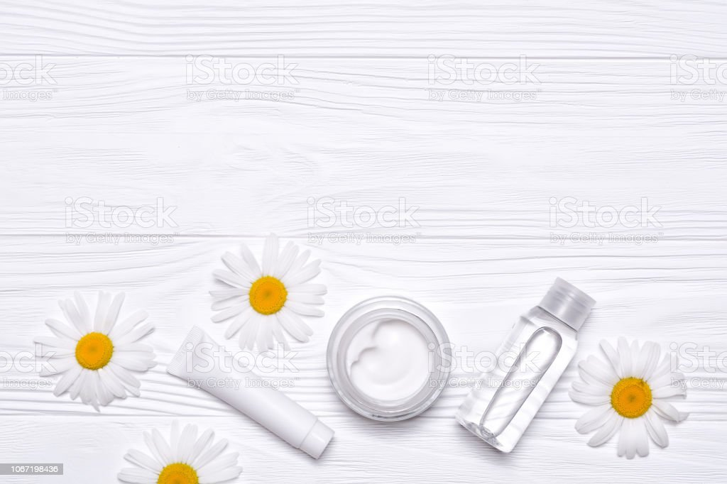 Bottles with cosmetics and daisy flowers on white wooden background....
