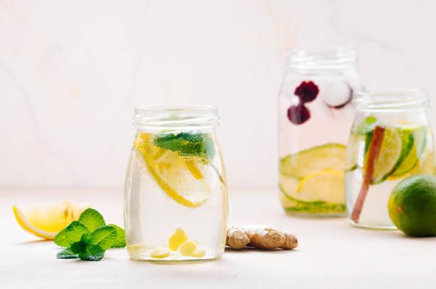 flaschen mit entgiftungswasser mit zitrone, ingwer und minze - ingwerwasser zubereiten stock-fotos und bilder