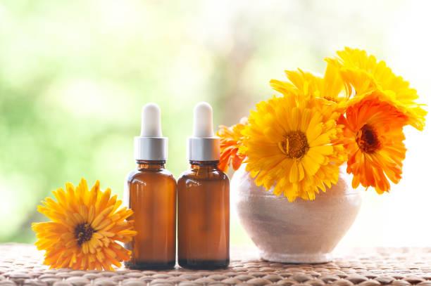 Garrafas com óleo de calêndula flor na natureza backgraund, conceito de cosméticos de natureza orgânica, bio, - foto de acervo