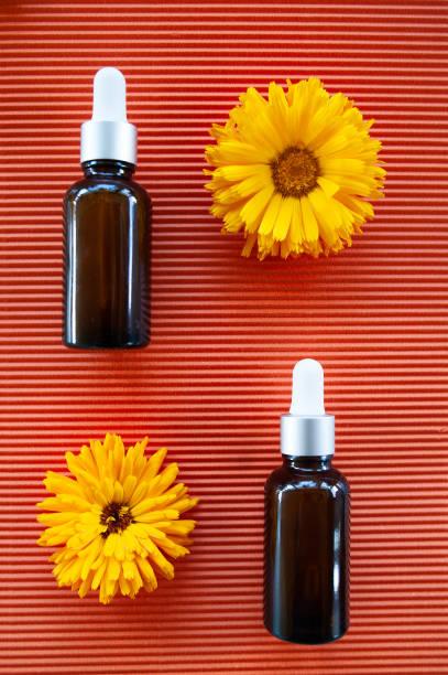 Garrafas com óleo de calêndula flor em laranja backgraund, conceito de cosméticos de natureza orgânica, geométrica, plana leigos, bio, - foto de acervo