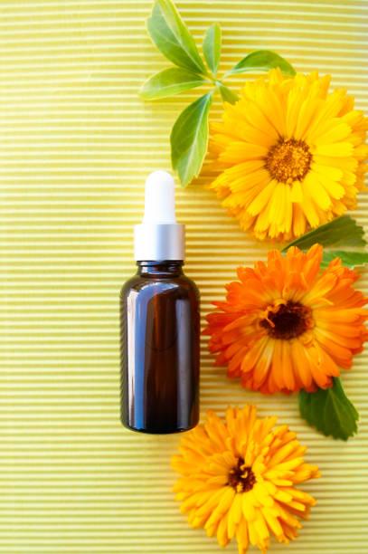 Garrafas com óleo de calêndula flor em backgraund amarelo, plana leigos, bio, orgânico, conceito de cosméticos de natureza - foto de acervo