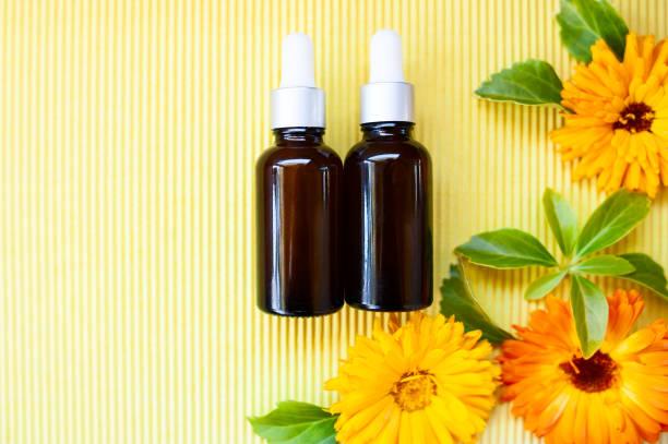 Garrafas com óleo de calêndula flor em backgraund amarelo, plana leigos, bio, orgânico, conceito de natureza cosmética, com espaço de cópia - foto de acervo