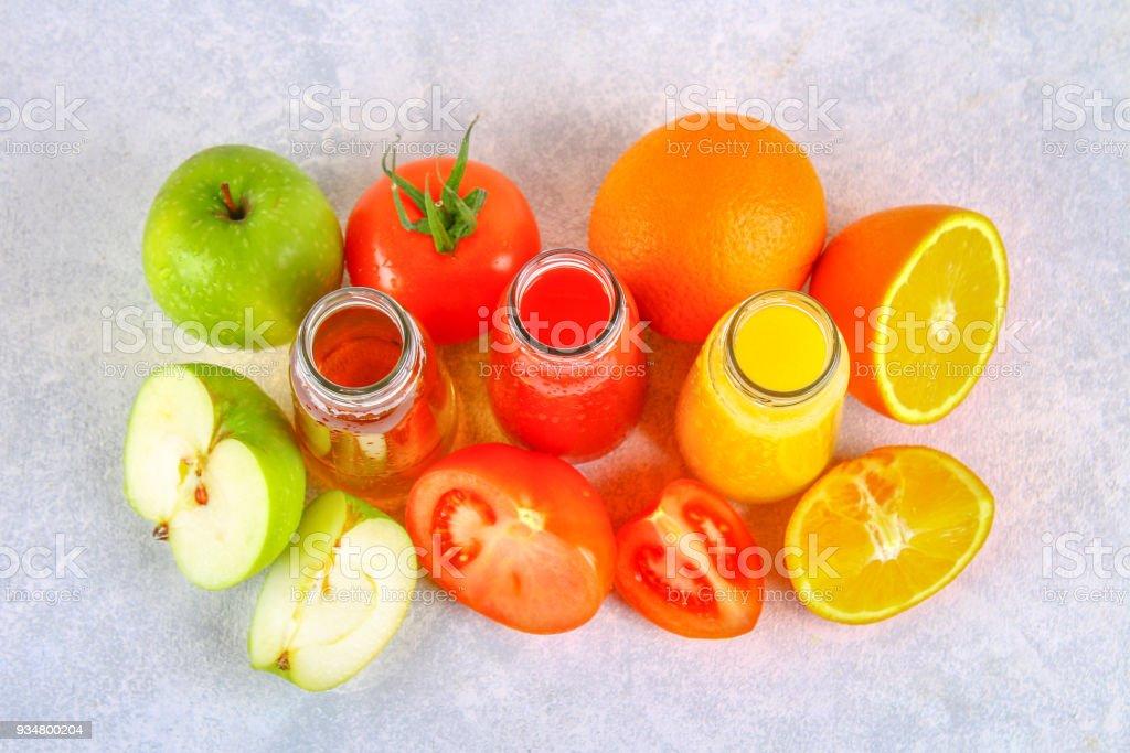 신선한 오렌지, 사과, 토마토 주스는 회색 콘크리트 테이블에 병. 주위 청과 최고의 볼 수 있습니다. - 로열티 프리 0명 스톡 사진