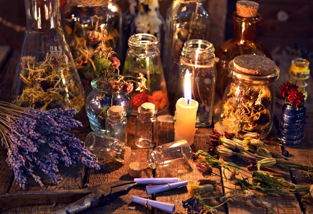 Bottles with herbs, lavender flowers, paper scrolls and magic objects stock photo