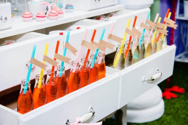 flaschen mit limonade und leeren etiketten in der linie in einem buffet - partylabels stock-fotos und bilder