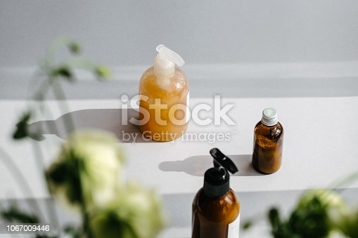istock Bottles with organic cosmetics in light and shadows 1067009446