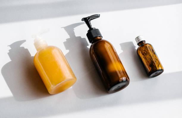 flaschen mit bio-kosmetik-overhead - glaswaschtisch stock-fotos und bilder