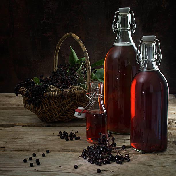 bottles with the red juice from black elderberries, dark background - roter holunder stock-fotos und bilder