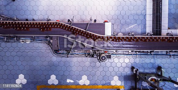 Industry, Business, Factory, Bottling Plant - Bottles Filled with Fresh Drink Moving on a Conveyor Belt to the Packaging Section of a Factory.