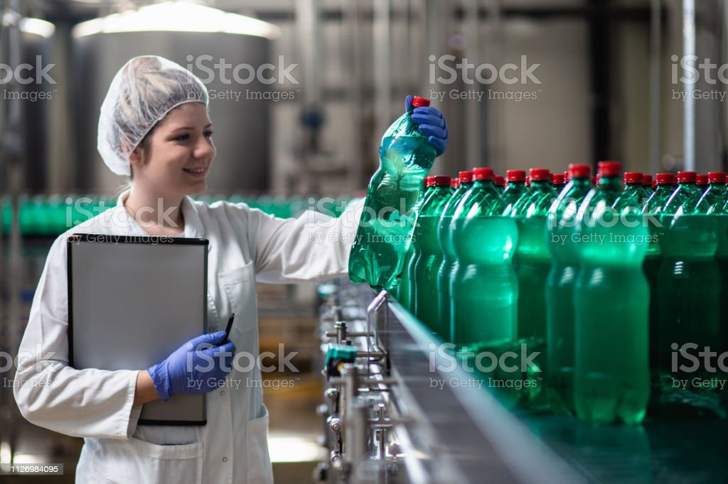 Young happy female worker in bottling factory checking water bottles...