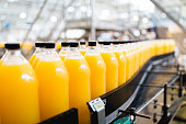 Bottling factory - Orange juice bottling line for processing and bottling juice into bottles. Selective focus.