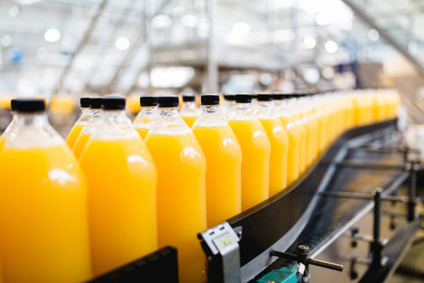 Bottling plant Bottling factory - Orange juice bottling line for processing and bottling juice into bottles. Selective focus. manufacturing stock pictures, royalty-free photos & images