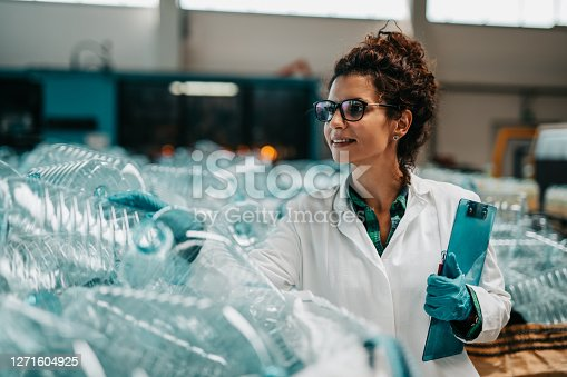 Young happy female worker in bottling factory recycling department. Inspection quality control.