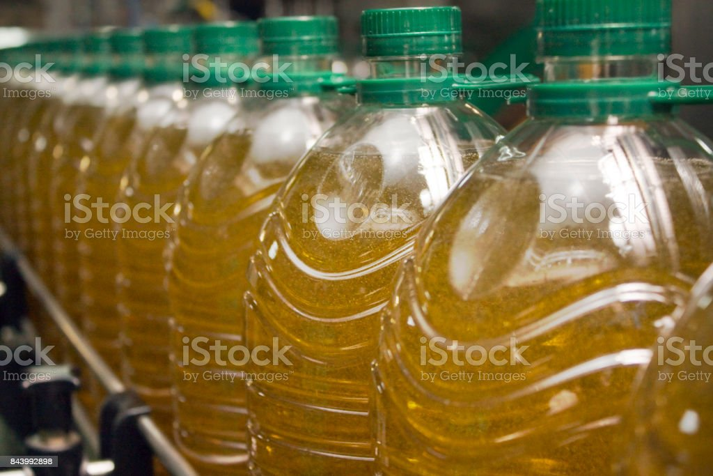 Bottling plant, close-up side view of row of large plastic bottles on...