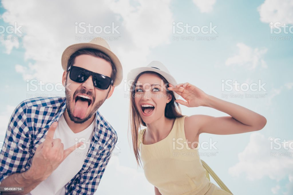 Bottom low angle view of foolish crazy cool funny cheerful joyful couple over sky background, handsome man showing rock and roll sign with fingers hand beautiful woman with open smile grimace royalty-free stock photo