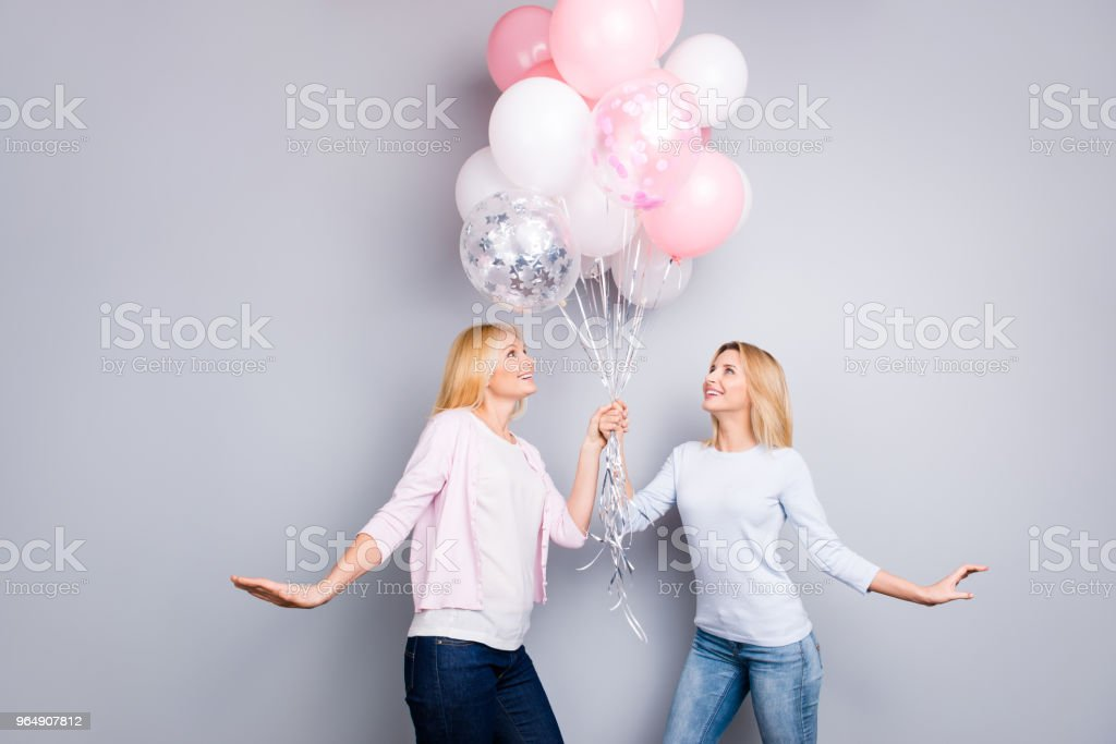 Bottom low angle view portrait of excited cheerful hopeful dreamy mother and daughter in jeans holding pink white air balloons in hands looking at present gift isolated on grey background royalty-free stock photo