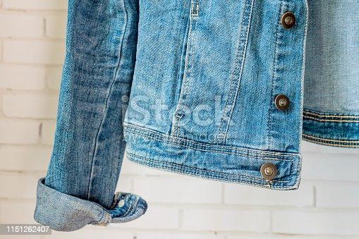 istock bottom of Blue denim woman jacket. Clothes fragment 1151262407