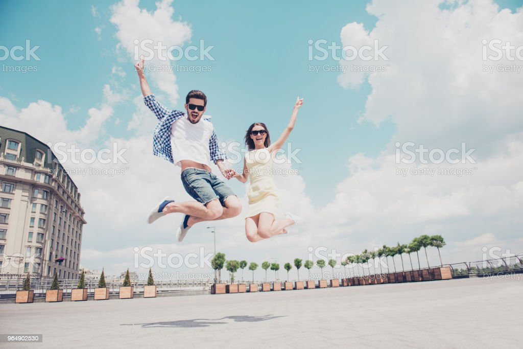 Bottom view low angle of funny crazy cheerful stylish trendy couple  holding hands jumping in the air showing two fingers, peace symbols, shouting screaming over sky clouds outdoor background royalty-free stock photo
