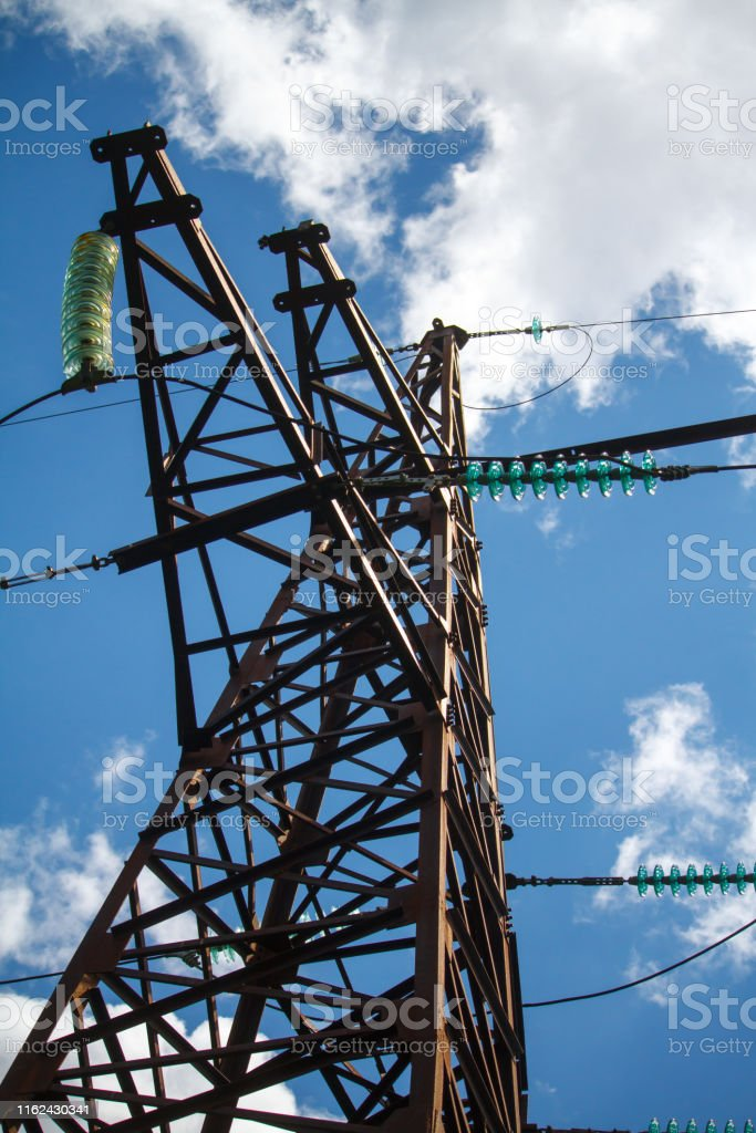A bottom view of a metal pole of a power line with a multitude of...