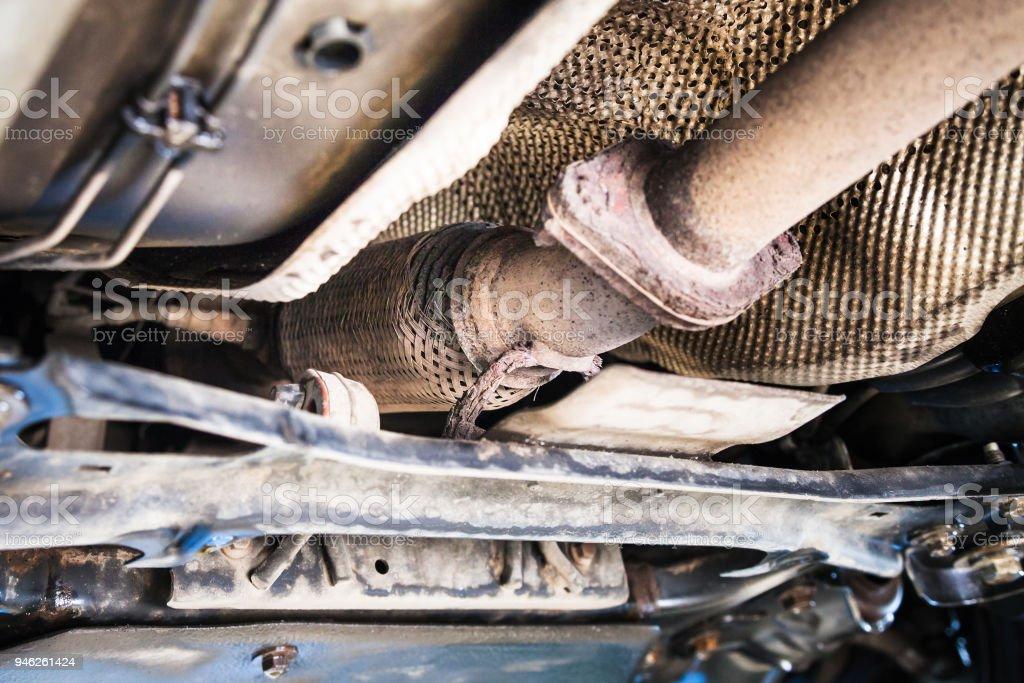 bottom view of broken corrugation muffler on car stock photo