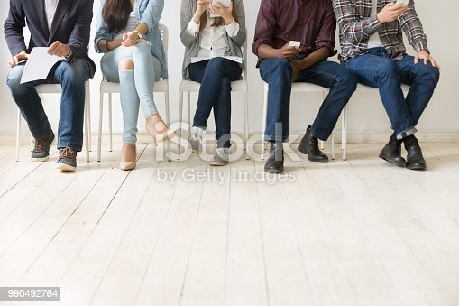 Close up view of diverse work applicants sitting together, holding smartphones, tablets and papers getting ready for interview, multiethnic candidates waiting in queue. Employment, hiring concept