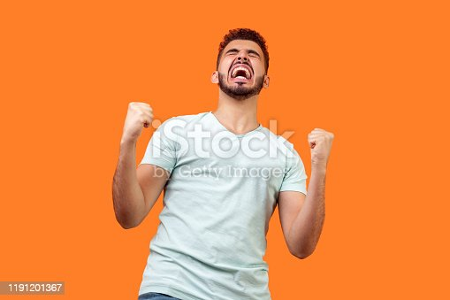 istock Bottom view of ecstatic motivated brunette man raised fists and shouting for joy. indoor studio shot isolated on orange background 1191201367