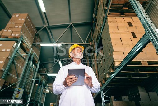 istock Bottom view of gray bearded worker in white uniform and protective helmet on head holding tablet and looking up while standing in warehouse. 1132357680