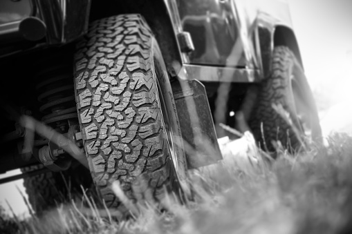 Bottom view of large off-road car wheel on landscape - black and white image