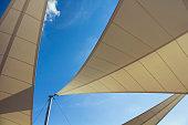 底面の三角形の形の大きな日よけとトルコのエーゲ海沿岸の都市であるボドルムの背景の青い空をオフに。