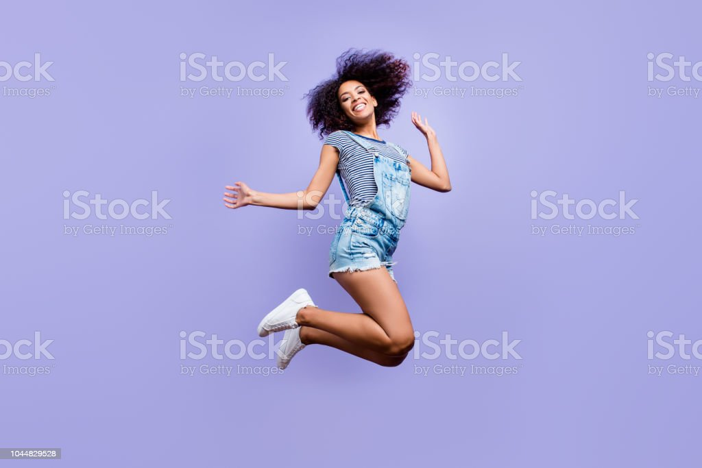 Bottom view portrait of crazy positive girl in jeans outfit jumping in air enjoying daydream having weekend vacation holiday isolated on violent background. Luck success concept Bottom view portrait of crazy positive girl in jeans outfit jumping in air enjoying daydream having weekend vacation holiday isolated on violent background. Luck success concept Adult Stock Photo
