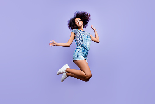 Bottom View Portrait Of Crazy Positive Girl In Jeans Outfit Jumping In Air Enjoying Daydream Having Weekend Vacation Holiday Isolated On Violent Background Luck Success Concept Stock Photo - Download Image Now