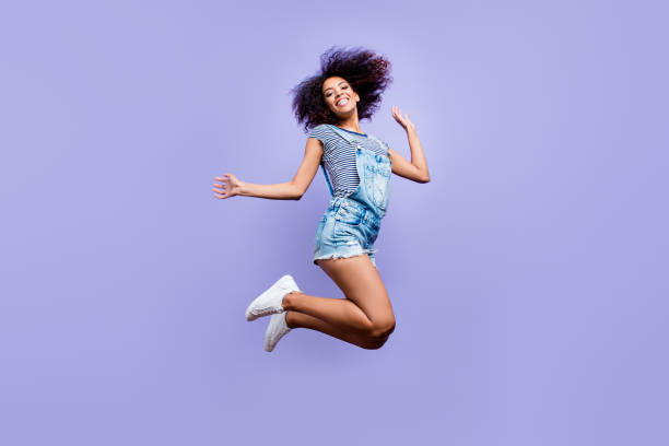 Bottom view portrait of crazy positive girl in jeans outfit jumping in air enjoying daydream having weekend vacation holiday isolated on violent background. Luck success concept Bottom view portrait of crazy positive girl in jeans outfit jumping in air enjoying daydream having weekend vacation holiday isolated on violent background. Luck success concept bib overalls stock pictures, royalty-free photos & images