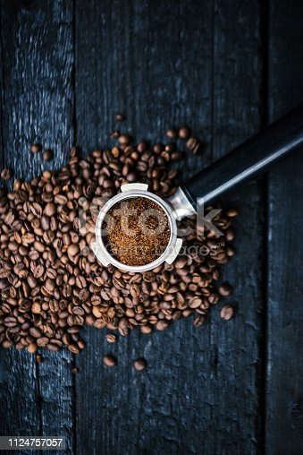 istock Bottomless filter with grind beans on a wooden black table. Roasted coffee beans. Espresso coffee extraction. Prepare of espresso. 1124757057