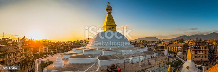 The iconic mandala dome of Boudhanath stupa, illuminated by warm sunset light as crowds of pilgrims and tourists walk around the ancient Buddhist shrine, a UNESCO World Heritage Site in Kathmandu, Nepal's vibrant capital city.