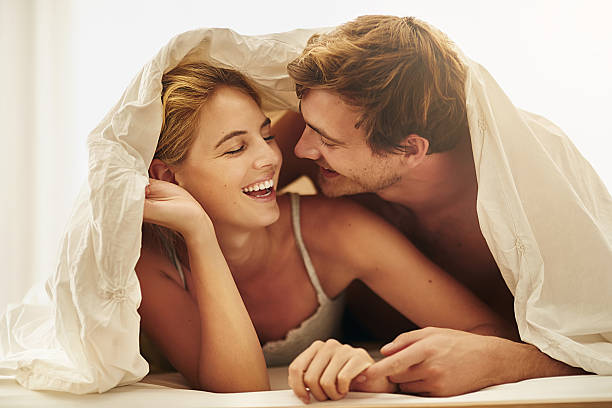 Boudoir shenanigans Shot of a young couple sharing an intimate moment under the covers in bed real couples making love stock pictures, royalty-free photos & images